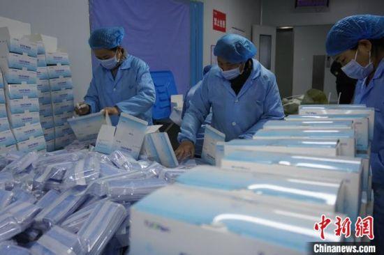 图为工人将封装好的口罩装盒装箱。 阚力 摄