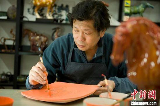 图为工作中的河南省政协委员、洛阳三彩艺术博物馆馆长郭爱和。洛阳三彩艺术博物馆供图