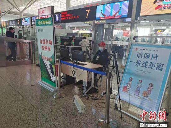 图为郑州东站工作人员正在对进出站旅客实时测温。 赵依婷 摄