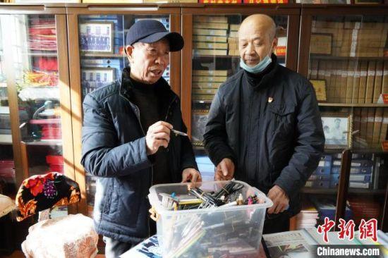 图为王春玉展示写日记用过的部分笔。 阚力 摄