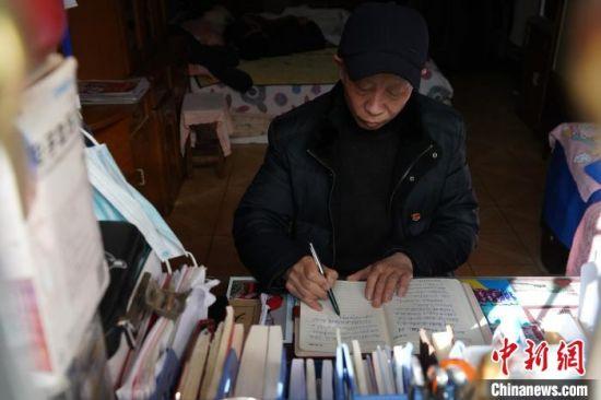 图为王春玉在日记本上记下当天的采访情况。 阚力 摄