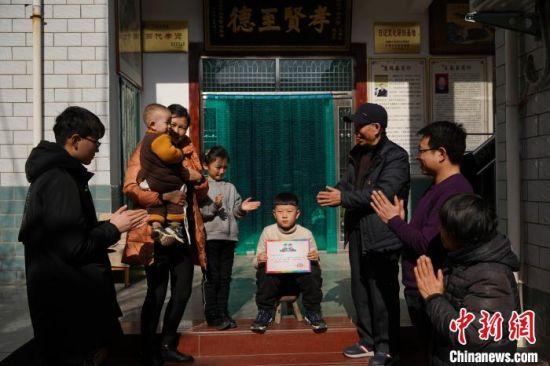 """图为王春玉的孙子获得王家最高荣誉――――颁奖、坐""""光荣凳""""。 阚力摄"""