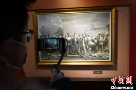 """图为游客对一幅""""二七大罢工""""主题画作进行拍摄。 阚力 摄"""