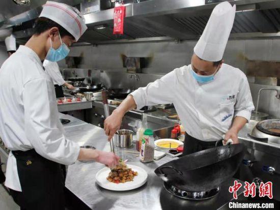 厨师正在将刚出锅的菜肴进行装盘 李明明 摄