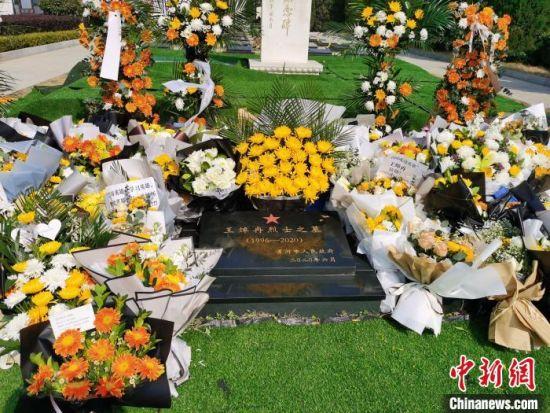 烈士王焯冉的墓碑旁边放满了鲜花。 王登峰 摄