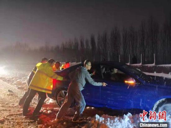 河南境内高速路段,路面执勤人员帮助滞留司机推车。河南省交通运输厅供图