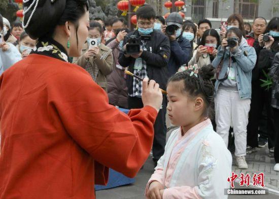 """4月3日,清明假期首日,河南省开封市举行敬圣人、点朱砂等传统礼仪的""""成童礼""""。""""成童礼""""是古代中国教育子女的一种礼仪。图为老师为儿童点朱砂。 中新社记者 阚力 摄"""