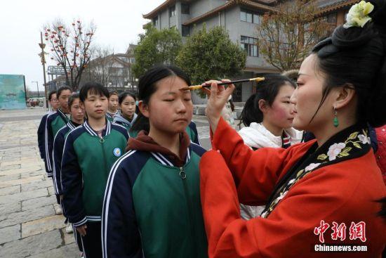 """4月3日,清明假期首日,河南省开封市举行敬圣人、点朱砂等传统礼仪的""""成童礼""""。""""成童礼""""是古代中国教育子女的一种礼仪。图为老师为学生点朱砂。 中新社记者 阚力 摄"""