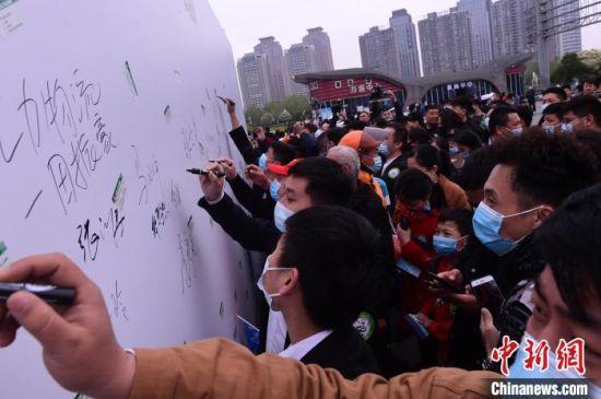 图为市民在守法出行承诺签名墙上签名。 周甬 摄