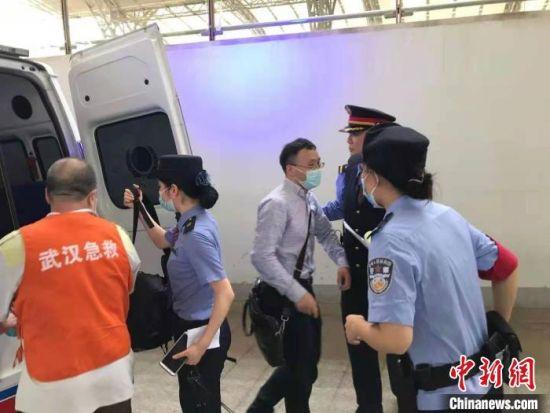 姚文龙(中间戴眼镜男士)与乘警一同将晕倒乘客送上救护车才离去。 郑州铁路公安处供图