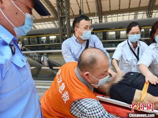 参与救援的姚文龙医生和陈姓护士互送晕倒乘客上救护车。 郑州铁路公安供图