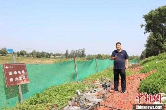 9月9日,比干庙景区负责人介绍围墙受损情况。 中新社记者 阚力 摄