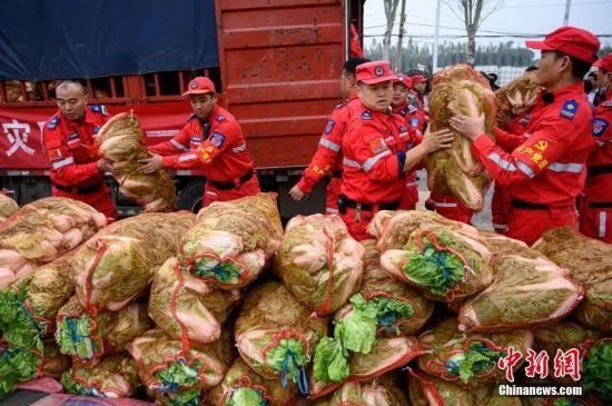 10月12日,山西省介休市,来自河南卫辉灾后复种的1.3万斤蔬菜运至山西洪灾地区,村民卸运物资。今年7月,卫辉市遭遇特大暴雨袭击,中国各地的救援力量驰援卫辉,其中就有来自介休市的救援队伍和救灾物资。近日,山西多地遭遇洪涝灾害,卫辉市立即组织救援队伍,携1.3万斤蔬菜,以及各类救灾物资驰援介休市受灾地区。河南卫辉这次捐赠的1.3万斤蔬菜,来自该市曾受灾地区之一的上乐村镇,也是当地农民灾后复种的蔬菜。 中新社记者 韦亮 摄